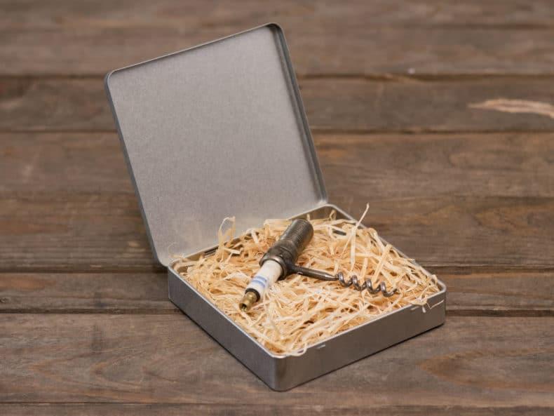 Korkenzieher aus einer alten Zündkerze in eleganter Blechdose